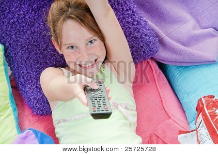 Young girl with chips in bed watching TV