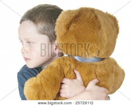 young boy cuddling stuffed bear