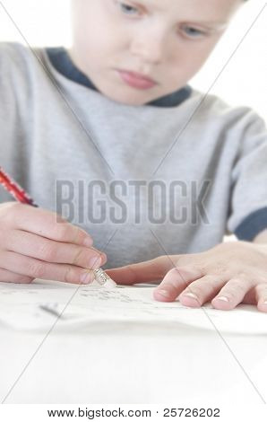 Shallow focus on pencil of boy erasing mistake