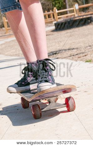 tomboy riding skateboard on sidewalk