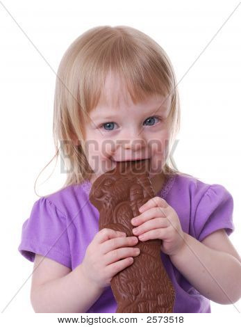 Little Girl Eating A Chocolate Easter Bunny