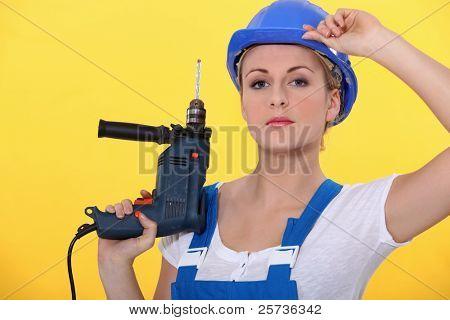 una mujer rubia vestida con un general posando con un taladro y ajuste su casco