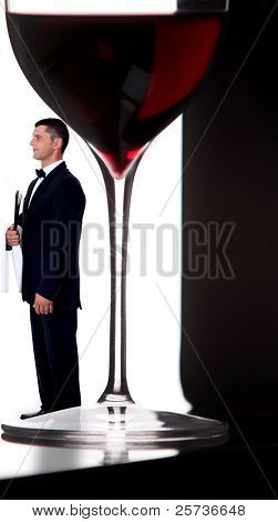 wine steward posing next to giant glass of wine