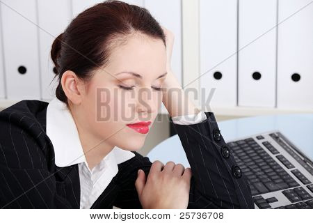 Beautiful caucasian businesswoman sleeping in the office.