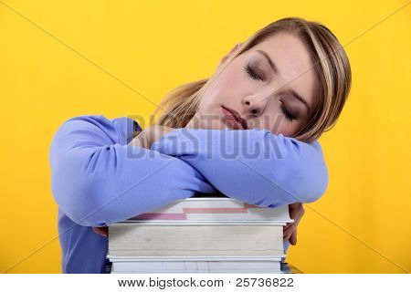 Student asleep on her books