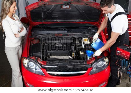 Professional auto mechanic and woman in auto repair shop. Garage.