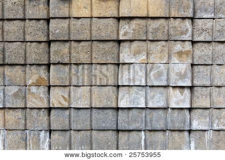 Wall or stack of gray abd tan concrete paver bricks
