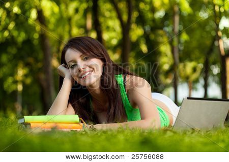 smiling brunette  woman laying on grass