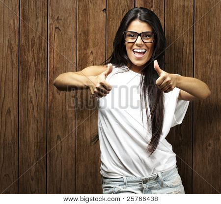 young woman doing good symbol against a wooden wall