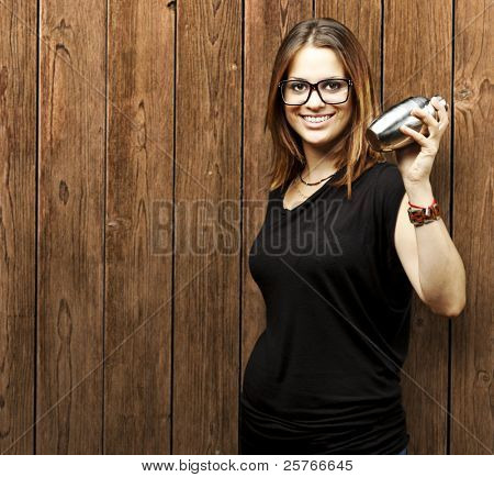 portrait of young woman with cocktail shaker against a wooden wall