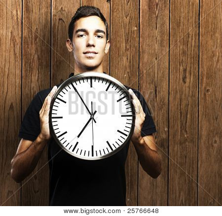 portrait of young man holding clock against a wooden wall
