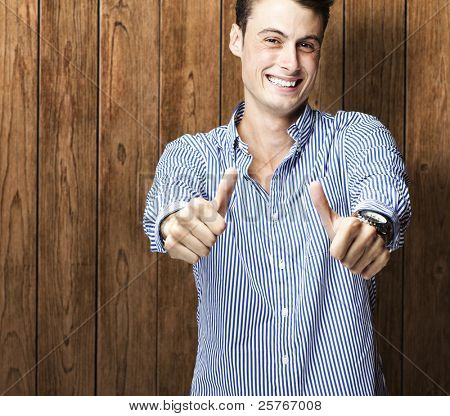 portrait of a happy young man against a wooden wall