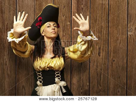 pirate woman gesturing stop against a wooden wall