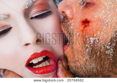 Close-up of wounded male face kissing woman on cheek, both faces covered with frost