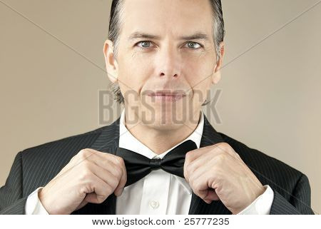 Confident Gentleman In Tux Adjusts Bowtie With Both Hands