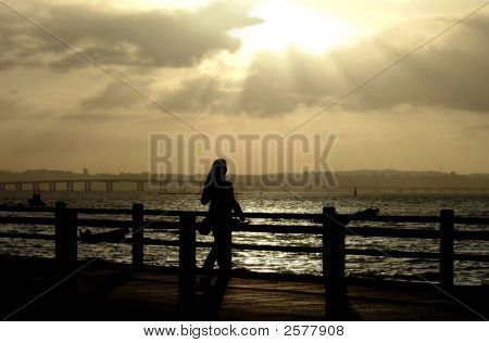 Woman Silhouette In Pier At Sunset
