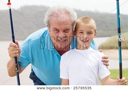 portrait of grandfather and grandson with fishing rods