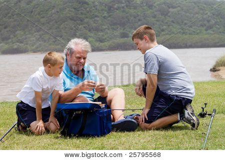 grandpa teaching grandsons how to put bait on fishing hook