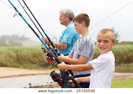 two young grandsons fishing with their grandpa by the lake