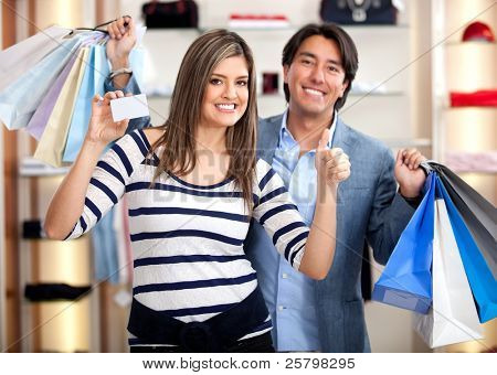 Shopping couple paying by credit card at a retail store