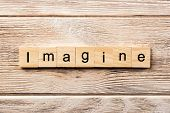 Imagine Word Written On Wood Block. Imagine Text On Table, Concept. poster