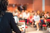 Female Public Speaker Giving Talk At Business Event. poster