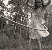 stock photo of hulahoop  - Young Girl Twirling Hula Hoop Outdoors in Sepia for Vintage Look - JPG