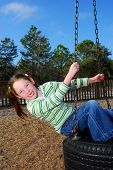 pic of tire swing  - Young Girl in Ponytails Missing front Teeth on Tire Swing - JPG