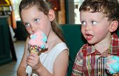 Cute boy and girl eating huge cones in ice cream parlor