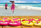 stock photo of spring break  - Kids running towards colorful flip flop sandals on boardwalk with ocean in distance - JPG