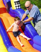 picture of inflatable slide  - Father helping young son on water slide - JPG