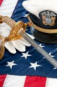 stock photo of corps  - military sword and gloves on US flag - JPG