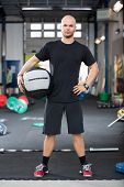 Determined Male Athlete Holding Medicine Ball In Health Club poster