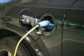 Electric Car Charging On Parking Lot With Electric Car Charging Station. Close Up Of Power Supply Pl poster