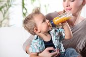 stock photo of chug  - Child drinking juice in his mother - JPG