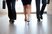 stock photo of section  - Low section of businesspeople walking along the office corridor - JPG