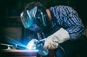 A Strong Man Welder In A Black T-shirt, In A Welding Mask And Welders Leathers Weld Metal Welding Ma poster