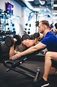 Young man assisting senior man at the gym. Personal trainer, retirement activities. poster