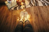Girl Legs In Stylish Warm Sock Sitting With Garland Lights At Christmas Tree With Gifts. Socks On Fl poster