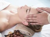 Head massage. Masseur doing massage the head of woman in a spa salon. poster