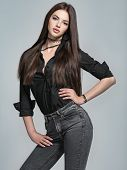 Young woman with long straight hair - at studio. Portrait of an attractive brunette girl. Fashion mo poster