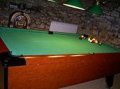 picture of jukebox  - Lit up pool table in rustic villa jukebox in background - JPG