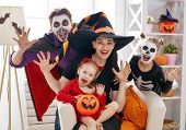 Mother, father and their kids having fun at home. Happy family celebrating Halloween. People wearing poster