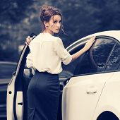 Young fashion business woman outside her car  Stylish female model with bun updo hair wearing white  poster