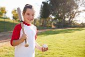 Young girl holding baseball and baseball bat looks to camera poster