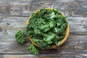 Fresh Green Curly Kale Leaves On A Wooden Table. Selective Focus. Rustic Style. Healthy Vegetarian F poster