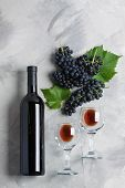 Bottle, Two Glasses Of Wine, Grape With Leaves On Grey Concrete Background. Concept Wine From Grapes poster