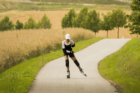 image of inline skating  - a woman on the rollerblades in front of landscape - JPG
