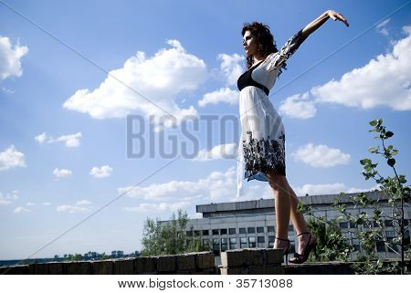 The Beautiful Woman In An Easy Years Dress On A Background Of The Blue Sky And Snow-white Clouds