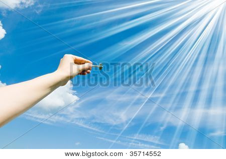 hand holding keys,blue skies in the background